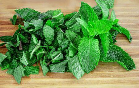 Fresh mint on wooden table,  copy space. Chopped Spearmint leaves Top view Banco de Imagens