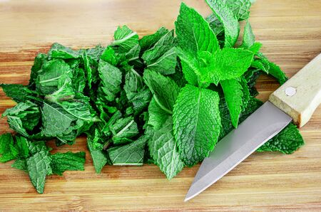 Fresh mint on wooden table, copy space. Chopped Spearmint leaves Top view