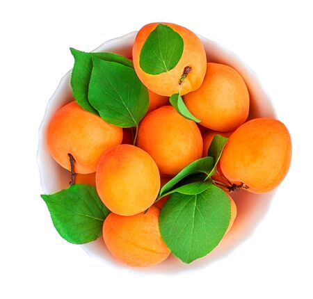 Apricots  isolated. Fresh Apricot with leaves in a bowl on white macro.  Top view Banco de Imagens