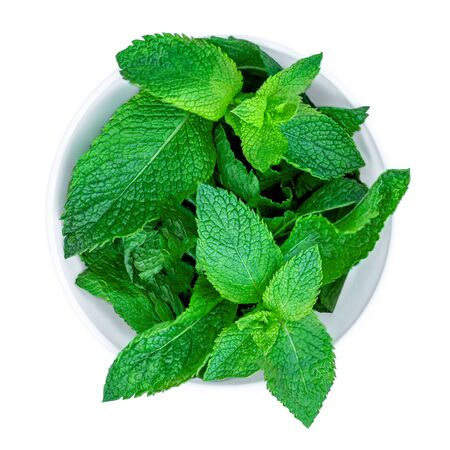 Fresh spearmint leaves isolated on the white background. Mint, peppermint in a bowl close up.Top view Banco de Imagens