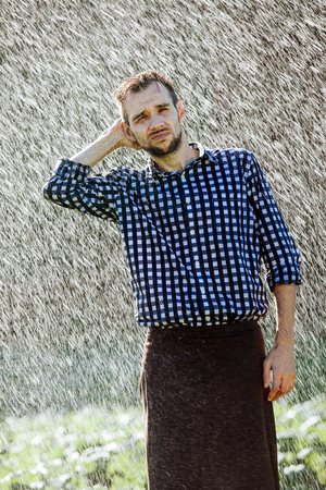 Portrait of a strong, drenched man in the rain. Young man getting wet under the rain in summer. Standard-Bild - 108670820