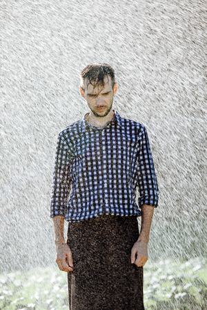 Portrait of a strong, drenched man in the rain. Young man getting wet under the rain in summer. Standard-Bild - 108670827