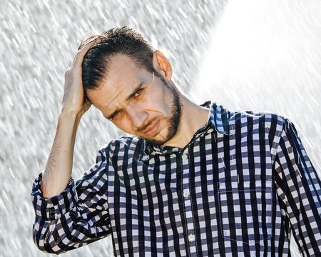 Portrait of a strong, drenched man in the rain. Young man getting wet under the rain in summer. Standard-Bild - 108670829
