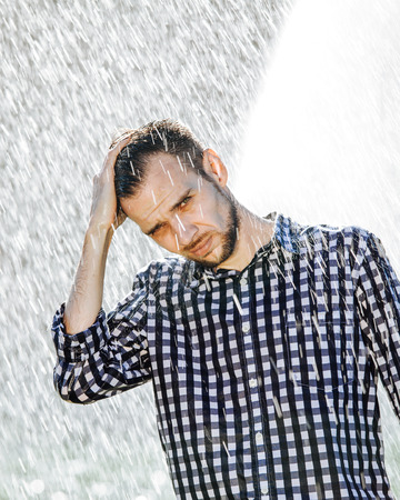 Portrait of a strong, drenched man in the rain. Young man getting wet under the rain in summer. Standard-Bild - 108670837