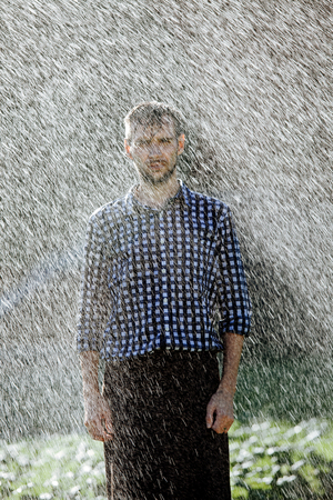 Portrait of a strong, drenched man in the rain. Young man getting wet under the rain in summer. Standard-Bild - 108670850