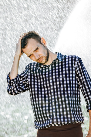Portrait of a strong, drenched man in the rain. Young man getting wet under the rain in summer. Standard-Bild - 108670852