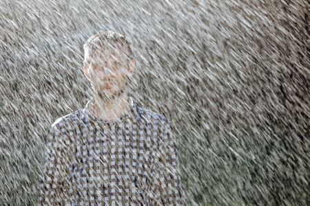 Porträt eines starken, durchnässten Mannes im Regen. Junger Mann, der im Sommer unter dem Regen nass wird.
