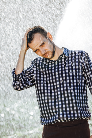 Portrait of a strong, drenched man in the rain. Young man getting wet under the rain in summer. Standard-Bild - 108670974