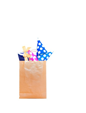 Shopping paper bag with gift boxes on the white background. Gift boxes with festive hats. Group of presents for party.