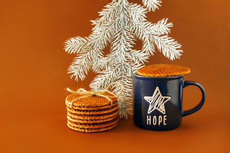 Dutch waffle called a stroopwafel on a yellow background with blue cup of tea or coffee and christmas tree. Reklamní fotografie