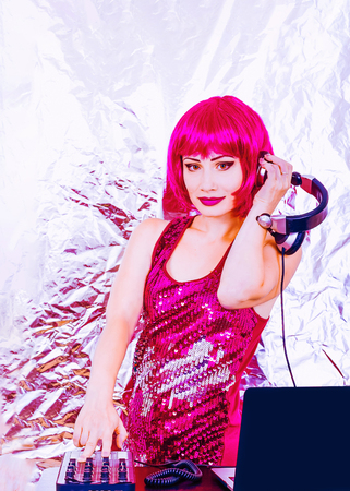 Glamorous DJ girl with pink hair and headphne on white background plays music disko. Sexy lady at the Valentine Day party.