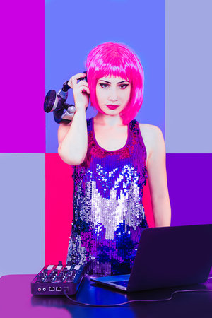 Glamorous DJ girl with pink hair and headphne on red, pink and blue background plays music disko. Stock Photo