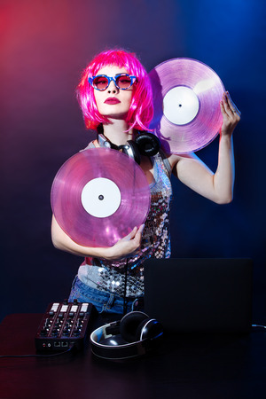 Portrait of a young woman with pink hair and vintage glasses on red and blue background. DJ woman with headphne and pink vinyls plays music disko. Glamour party on the equipment in the summer club.