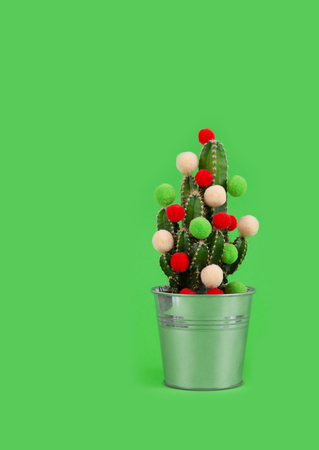 Funny holiday cactus tree with colored balls. Green tropical flower us a gift for celebration or party on the green background.