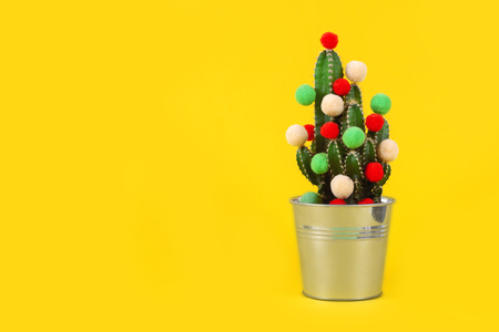Funny holiday cactus tree with colored balls. Green tropical flower us a gift for celebration or party on the yellow background.