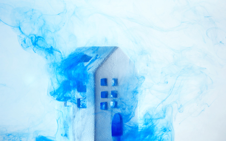 Small ceramic house under the water with blue acrylic paints. The concept of real estate, rent, sale or heating. White house from fairy tale.