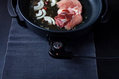 Electric pan with meat on the table. Independent auxiliary skillet for cooking any place.
