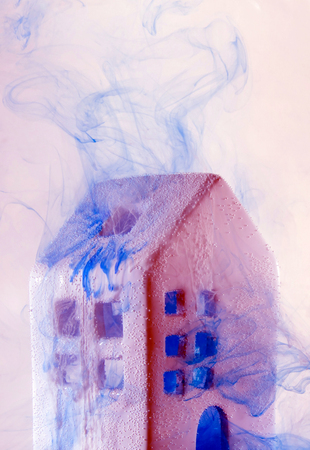 Small ceramic house under the water with violet acrylic paints. Fabulouse white ceramic house at the night with smoke from windows and doors. Stock Photo