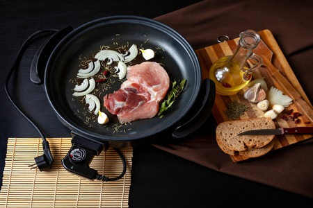 Electric pan with meat of pork on the table. Independent auxiliary skillet for cooking any place.
