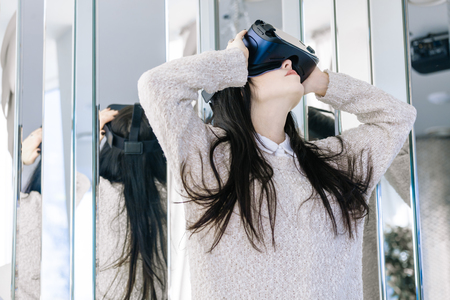 Young girl with headset on hir face gets acquainted with new technologies. Woman using the virtual reality headset.