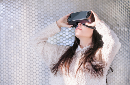 A young girl with a headset on the face meets new technologies. Woman using virtual reality headset.