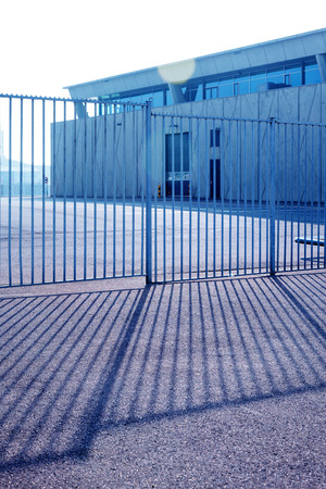 Workplace Fenced a fence with light and shadow. large warehouse against a sunlight and sky. Banque d'images - 117299570