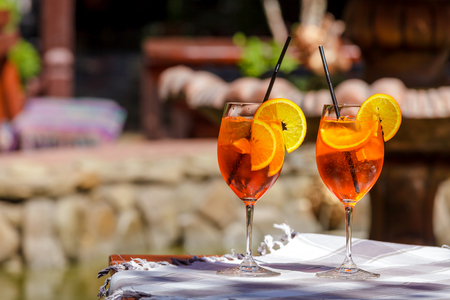 Aperol spritz cocktail in glass on the wooden table against a bright sunny cafe. Stock fotó