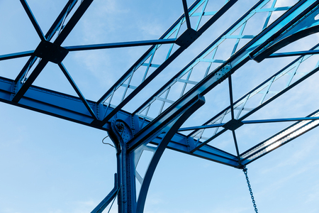 Details of modern fastening of the bridge. Modern architectural building awning against blue sky.