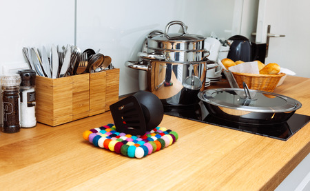 Clean pan and lots of pots on the yellow wooden kitchen table.