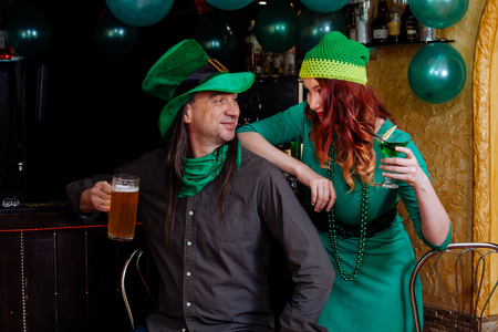 f2c0e0dde2d Stock Photo - The company of young girls and one man celebrate St. Patrick s  Day. They have fun at the bar. They are dressed in carnival headgear