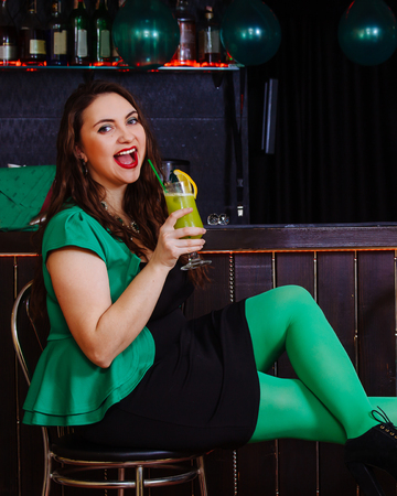 Young girl celebrate St. Patrick's Day. Woman have fun at the bar. A beautiful girl in a green hat and dress drinks a green cocktail.