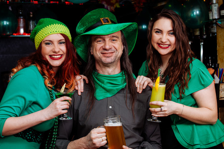 The company of young girls and one man celebrate St. Patrick's Day. They have fun at the bar. They are dressed in carnival headgear, green hats and clothes. Imagens