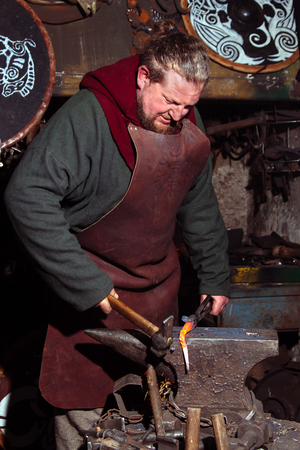Viking forges weapons and swords in the smithy. A man in a warriors clothes is in the smithy on the background of fire.