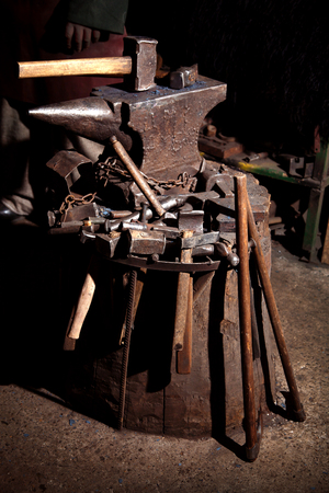 Viking sword handles in sword rack at Viking reenactment event. Many weapons of metal are in the forge on the anvil. 스톡 콘텐츠