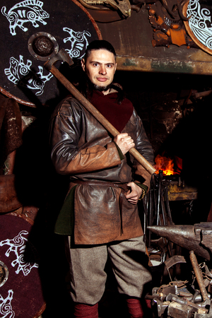 A man in a warrior's clothes is in the smithy on the background of fire. A sad Viking stands with a weapon in his hands. Archivio Fotografico
