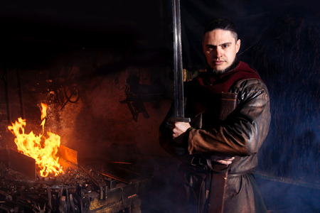 A man in a warriors clothes is in the smithy on the background of fire. Serious militant Viking stands with a weapon in his hands. Stock Photo