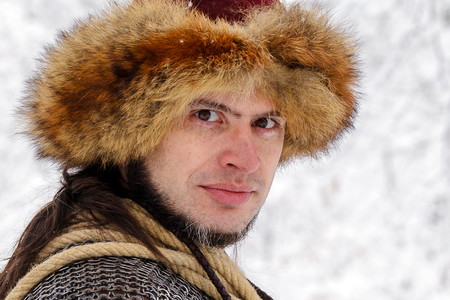 Portrait of a Viking Warrior Man. Viking warrior with chain mail leather spear walking in winter woods before battle, scandinavian traditional clothing for lumberjack, viking concept. Stockfoto