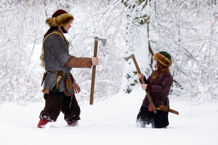 Father and son Vikings in a deep winter forest and the father teaches his son to be a real Viking. Viking warrior with chain mail leather spear walking in winter woods before battle, scandinavian traditional clothing for lumberjack, viking concept.