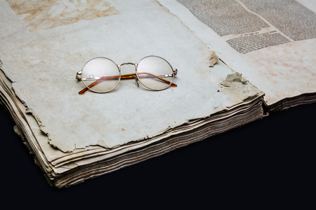 Old book cover, vintage texture, isolated on black background. On an open old book lie old golden round glasses. Old Jewish Talmud in Yiddish. 版權商用圖片