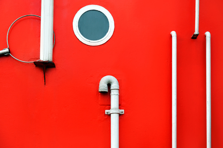 A close-up of side of ship with a porthole and handrails. Board the red ship. Red background with white marine details.