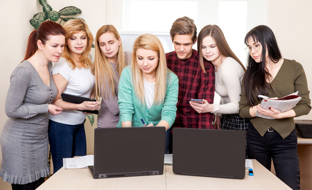 Business team at the work space with computers. Teacher in the class room teaches adults men and women.