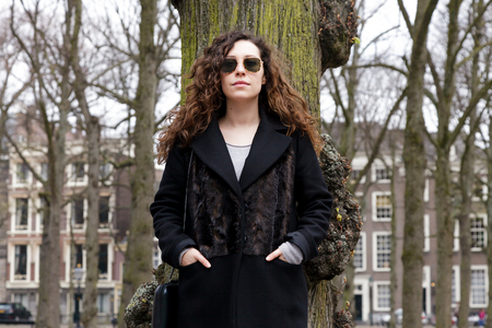 Young girl with long curly hair standing near a tree in the park. A woman in a coat and sunglasses in an old town in the spring. Zdjęcie Seryjne