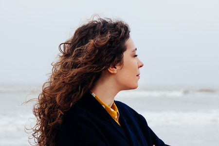 Close-up of a girl with long curly hair against a cold winter sea. Portrait of a woman on sea with strong wind and rain.