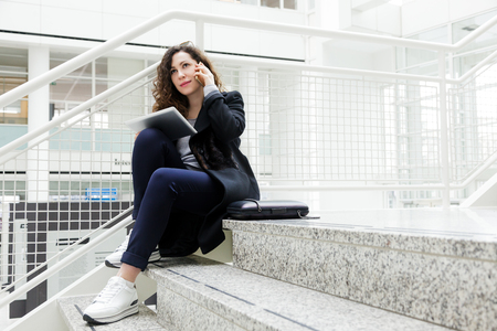A student is sitting on the steps in a white office and smiling. Beautiful business woman uses a tablet and speaks by phone .