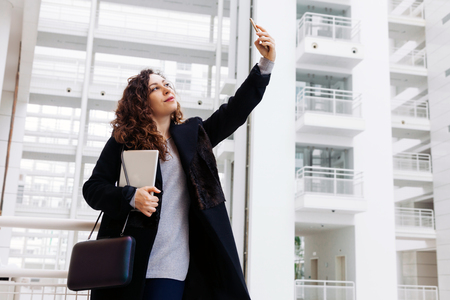 A student stands in a large white building and makes selfies on the phone. Beautiful business woman uses a tablet and speaks by phone. Foto de archivo