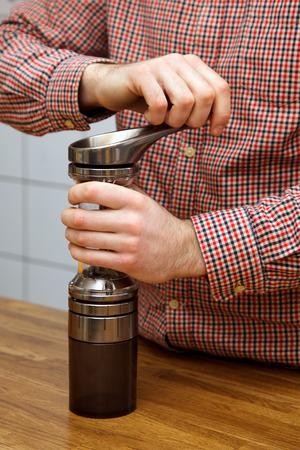 Die Hände der Männer machen Kaffee. Barista hackt Kaffee in einer Kaffeemühle.