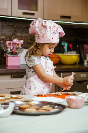 The little girls is in the kitchen near the table. Girl is going to decorate cookies with colored cream Фото со стока