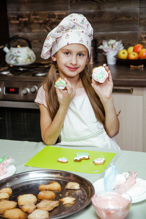 The little girls is in the kitchen near the table. Girl is going to decorate cookies with colored cream. A child is holding a cookie. Фото со стока
