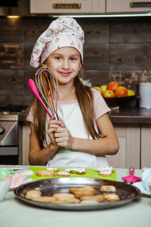 A little girl is in the kitchen near the table with a spoon in her hand. The girl is going to decorate cookies with colored cream