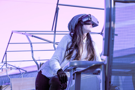 A young girl with a headset on the face meets new technologies. Woman using virtual reality headset on winter's street. 写真素材